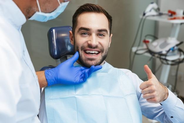 Apuesto joven feliz sentado en el centro médico dentista mostrando los pulgares para arriba