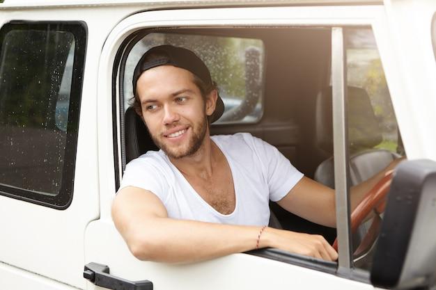 Apuesto joven con gorra de béisbol hacia atrás conduciendo un vehículo suv blanco, sacando el codo de la ventana abierta, sonriendo