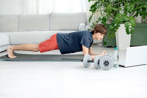 Apuesto joven hace deporte en casa y mira entrenamiento en línea
