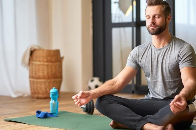 Apuesto joven haciendo ejercicio de meditación en casa