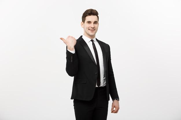 Apuesto joven hombre de negocios feliz sonrisa señalar con el dedo al espacio vacío de la copia, empresario mostrando el lado señalador, concepto de producto publicitario, aislado sobre fondo blanco.