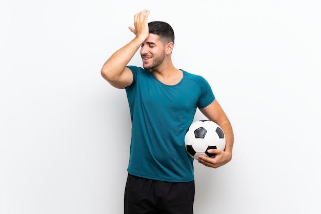 Apuesto joven jugador de fútbol hombre sobre pared blanca aislada se ha dado cuenta de algo y tiene la intención de la solución
