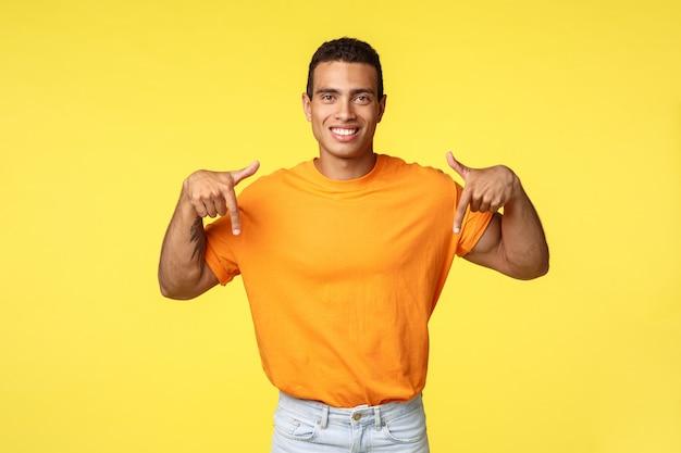 Apuesto joven masculino en camiseta naranja apuntando hacia abajo
