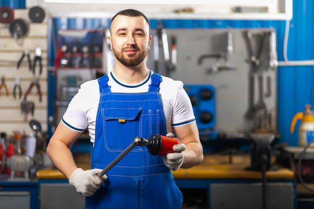 Apuesto joven mecánico de automóviles masculino en ropa especial uniforme está de pie y sosteniendo una llave de trinquete neumática en el fondo de bastidores y un escritorio con herramientas para reparación de automóviles.
