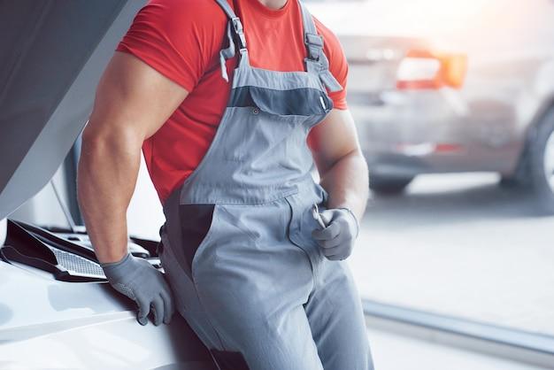 Apuesto joven mecánico de automóviles en uniforme está examinando el coche en auto servicio