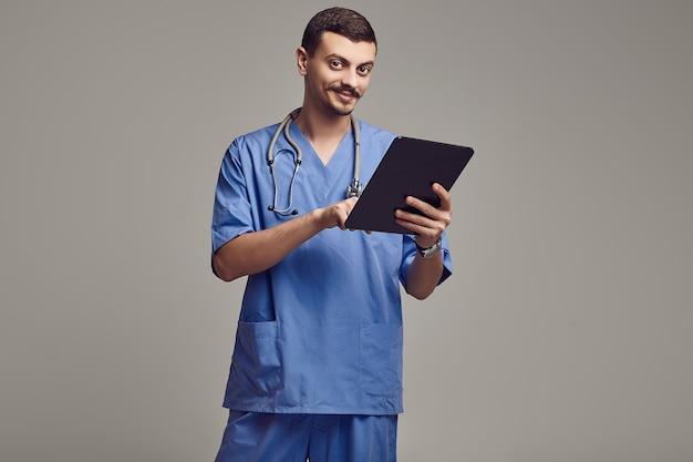 Apuesto joven médico árabe con elegante bigote en azul