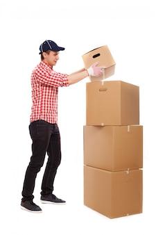 Apuesto joven mensajero con cajas marrones
