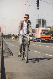 Apuesto joven montar bicicleta en la carretera de la ciudad