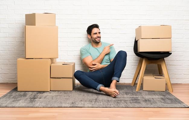Apuesto joven moviéndose en un nuevo hogar entre cajas apuntando con el dedo hacia un lado
