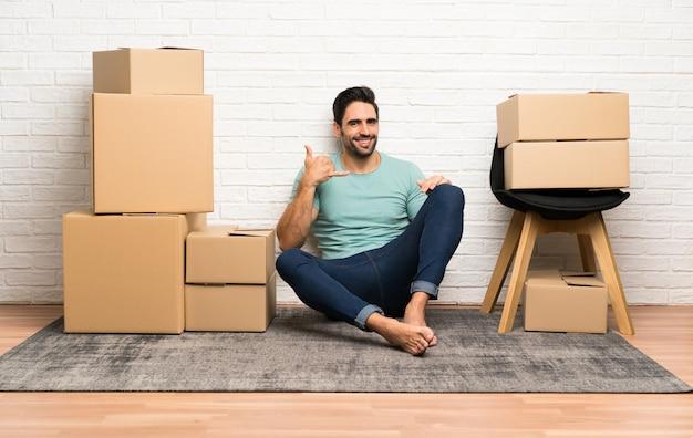 Apuesto joven moviéndose en un nuevo hogar entre cajas haciendo gesto de teléfono