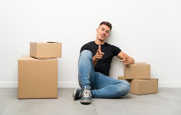 Apuesto joven moviéndose en un nuevo hogar entre cajas señala con el dedo