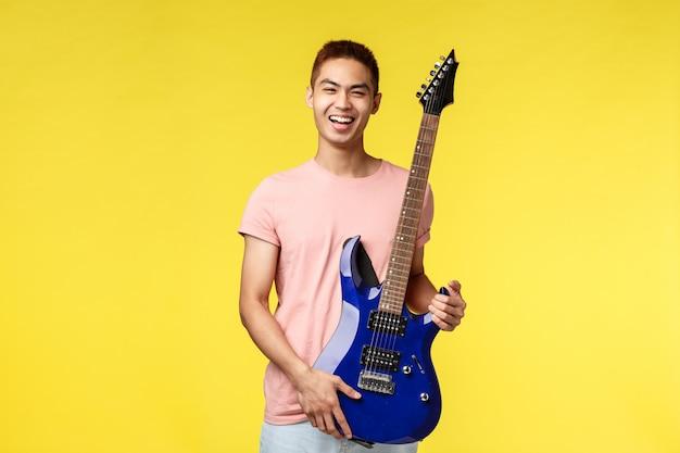 Apuesto joven músico tocando la guitarra y cantando, aislado