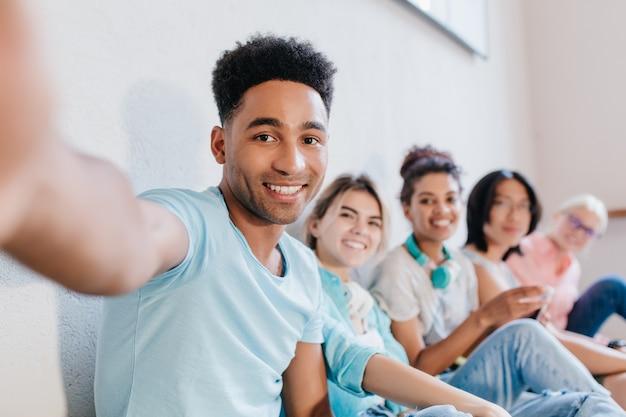 Apuesto joven negro con peinado rizado haciendo selfie con amigos y sonriendo. retrato interior de estudiantes riendo alegres divirtiéndose después de lección y tomando fotos.
