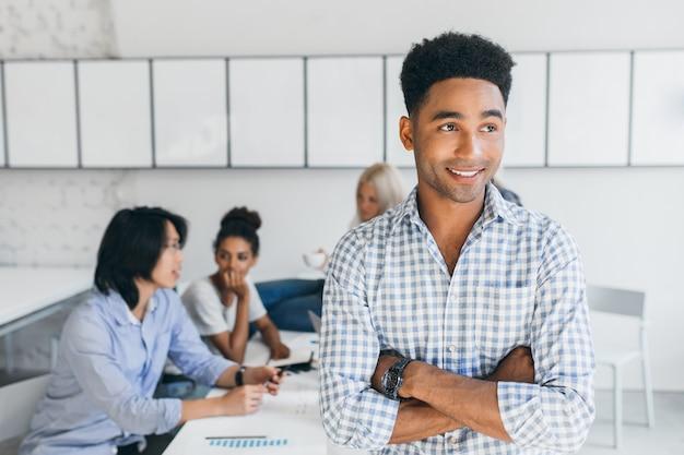 Apuesto joven negro en reloj de pulsera mirando a otro lado, mientras sus colegas discuten nuevas ideas. retrato interior de especialistas internacionales en ti con chico africano.