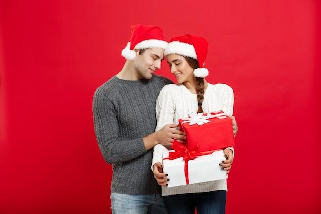 Apuesto joven novio en suéter de navidad sorpresa a su novia con regalos.
