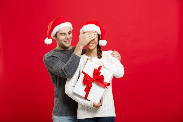 Apuesto joven novio en suéter sorpresa a su novia con el regalo blanco.