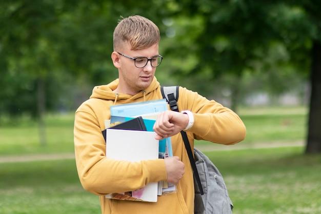Apuesto joven, ocupado estudiante universitario o universitario o alumno con libros, libros de texto y mochila con gafas mirando su reloj de pulsera, comprobando el tiempo a toda prisa, apresurándose a las lecciones, los exámenes. no hay tiempo.