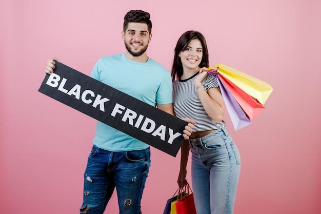 Apuesto joven pareja novio y novia con signo de viernes negro y coloridas bolsas de compras