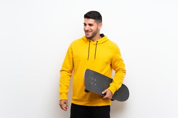 Apuesto joven patinador sobre pared blanca aislada sonriendo mucho