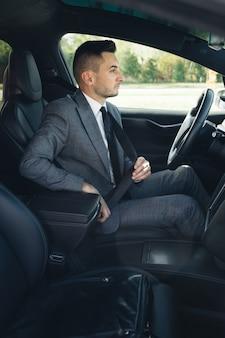 Apuesto joven pellizca el cinturón de seguridad
