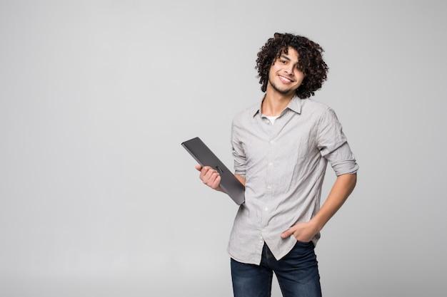 Apuesto joven de pelo rizado trabajando en equipo portátil de pie aislado en la pared blanca