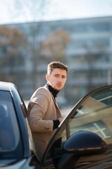Apuesto joven está de pie cerca de un nuevo coche moderno con puerta abierta en el soleado día de otoño