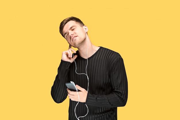 Apuesto joven de pie y escuchando música.