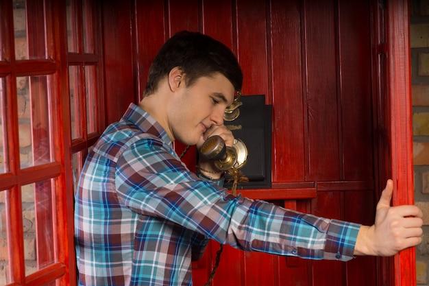 Apuesto joven de pie hablando por un auricular de teléfono vintage en una cabina apoyada en la puerta de madera abierta