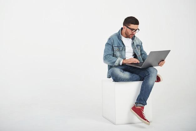 Apuesto joven con portátil y comprobar su horario en blanco
