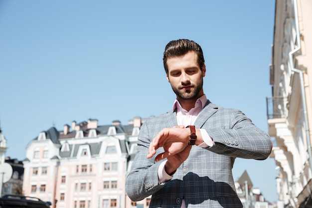Apuesto joven que controla la hora en su reloj de pulsera
