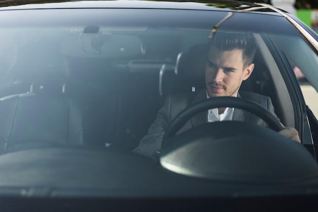 Apuesto joven que viaja en coche de lujo
