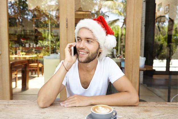 Apuesto joven con rastrojo con capuchino sentado en la mesa de café de madera y saludando a amigos en navidad, usando teléfonos inteligentes.