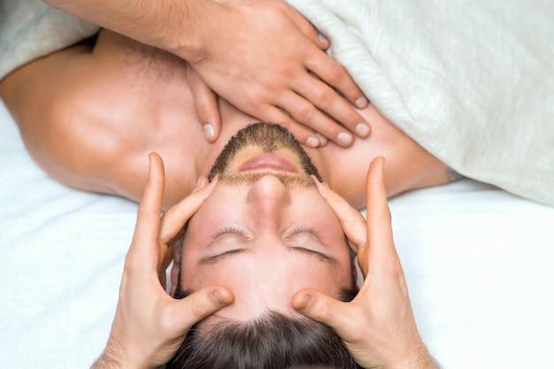 Apuesto joven recibiendo un masaje en la cabeza de dos masajistas.