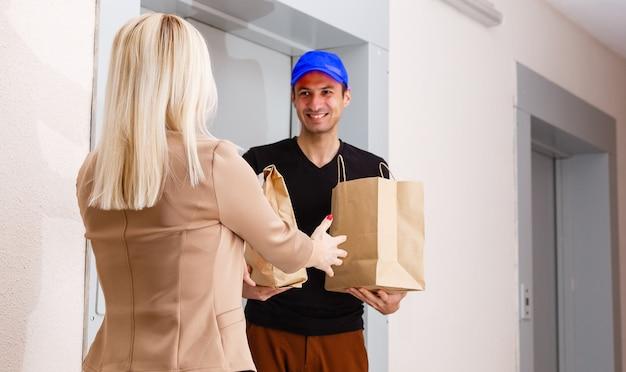 Un apuesto joven repartidor entregando un paquete al apartamento