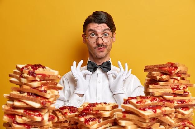 Apuesto joven rodeado de sándwiches de gelatina de mantequilla de maní