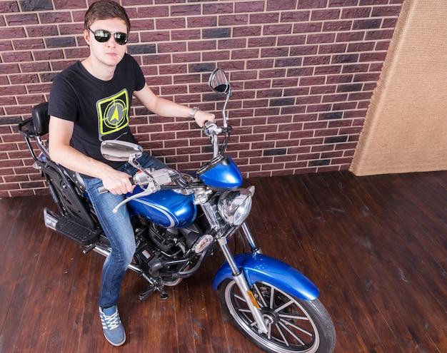 Apuesto joven, en ropa casual con sombras, en su motocicleta azul, mirando a la cámara.