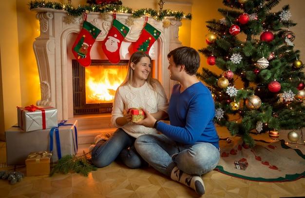Apuesto joven sentado en la chimenea con la mujer y dándole su regalo de navidad