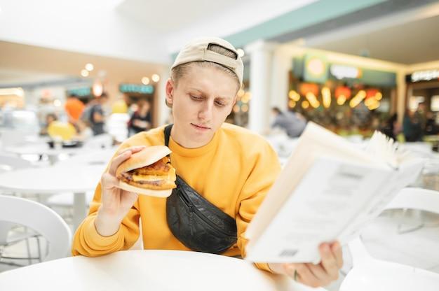 Apuesto joven sentado en un restaurante de comida rápida con un libro y una hamburguesa en la mano