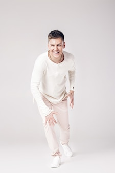 Apuesto joven sonriente con un suéter blanco está listo para correr hacia adelante.