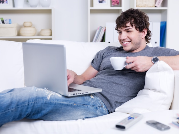 Apuesto joven sonriente con taza de café usando la computadora portátil en casa