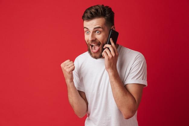 Apuesto joven sorprendido hablando por teléfono móvil hace gesto de ganador.
