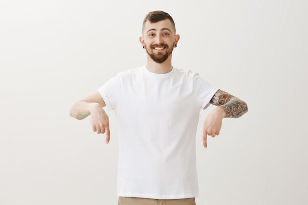 Apuesto joven con tatuajes apuntando con el dedo hacia abajo en el anuncio