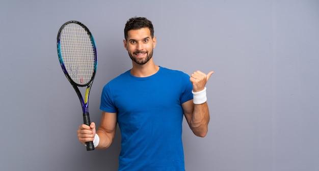Apuesto joven tenista hombre apuntando hacia un lado para presentar un producto