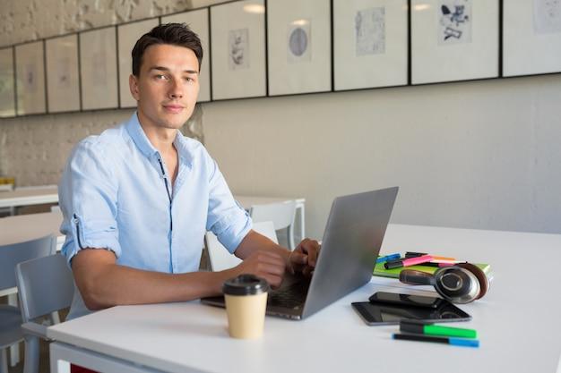 Apuesto joven trabajando en la computadora portátil, escribiendo, trabajo independiente en línea