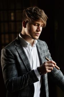 Apuesto joven en traje gris está parado con un cigarro