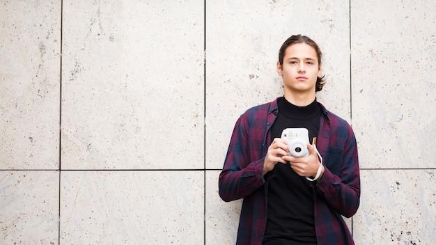 Apuesto joven viajero sosteniendo una cámara