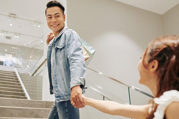 Apuesto joven vietnamita sonriente con bolsas de la compra de la mano de la novia y subir las escaleras