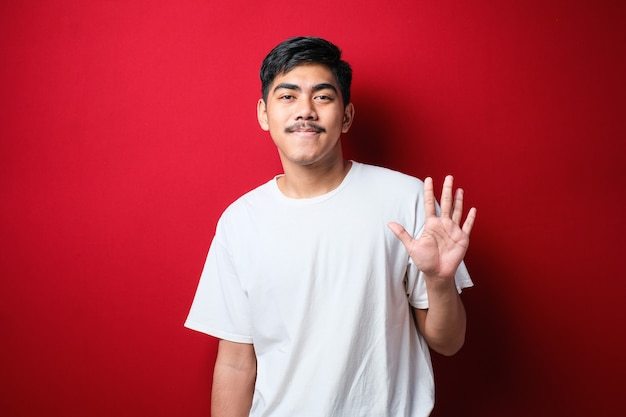 Apuesto joven vistiendo ropa casual mostrando y apuntando hacia arriba con los dedos número cinco mientras sonríe confiado y feliz sobre fondo rojo.