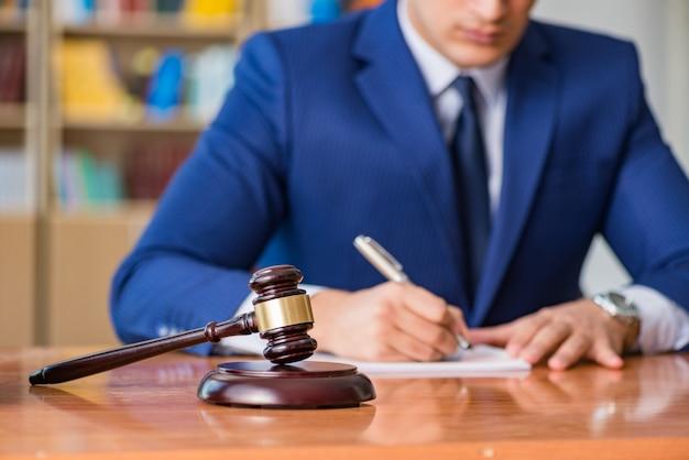 Apuesto juez con martillo sentado en la sala del tribunal