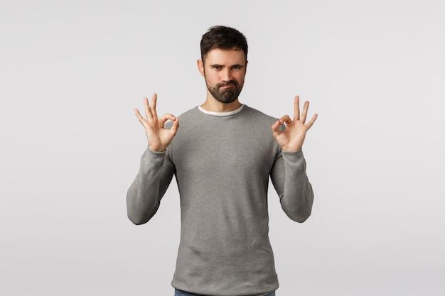 Apuesto y masculino, hombre macho barbudo con suéter gris, sonrisa burlona y entrecerrando los ojos complacido, alaba la buena elección, muestra bien, aprobación o gesto aceptable, producto de calidad perfecta satisfecho,